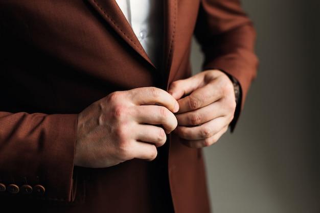 Primo piano dello sposo per pizzicare un'elegante giacca marrone