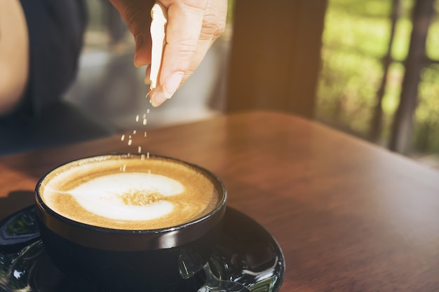 Primo piano dello zucchero di versamento della signora mentre preparando la tazza di caffè calda