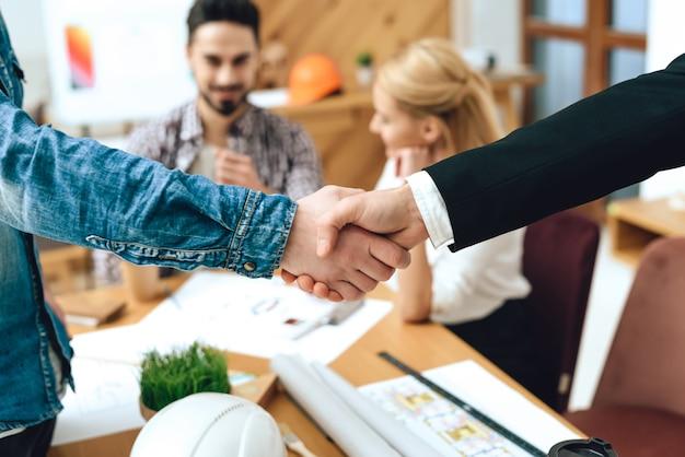 Primo piano designer e architetto si stringono la mano.