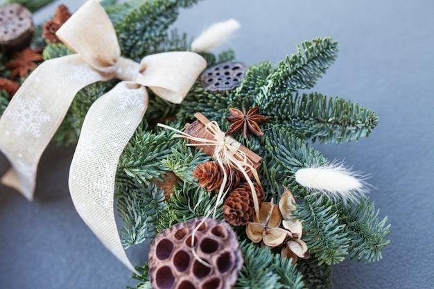 Primo piano dettagli della corona di natale fatta di rami di abete naturale. ghirlanda con ornamenti naturali: dossi, noci, cannella, coni. decorazioni natalizie.