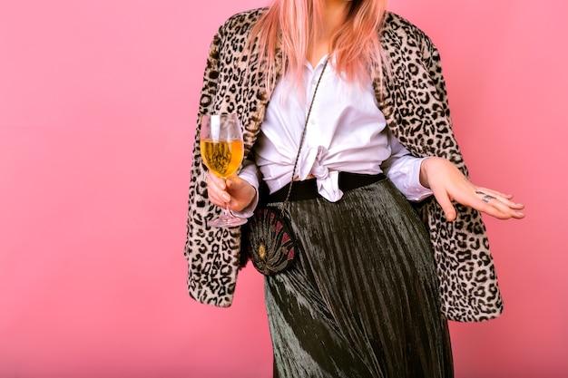Primo piano dettagli di moda in studio, giovane donna elegante che indossa un abito da sera elegante, classica camicia bianca, gonna scintillante e mini borsa vintage, cappotto di leopardo di pelliccia, bere champagne e ballare.