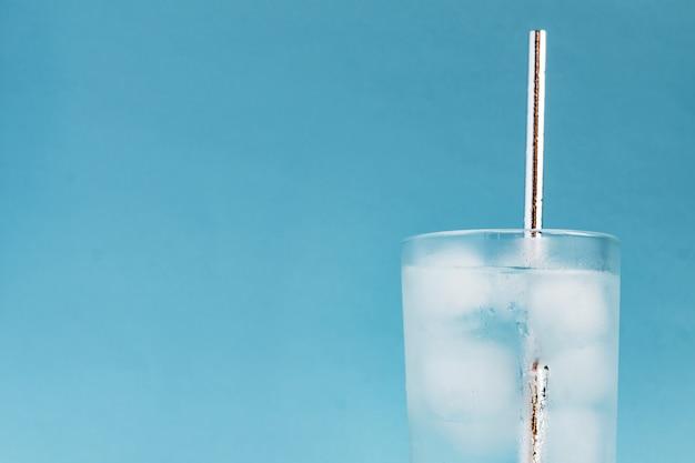 Primo piano di acqua pura con ghiaccio e paglia di carta argento in alto vetro trasparente e luce vivida del sole. copia spazio