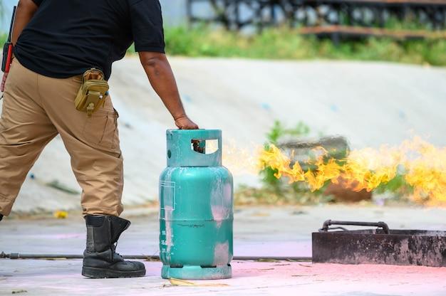 Primo piano di addestramento inferiore del corpo dei vigili del fuoco per esercitazione antincendio dimostrando come chiudere gas