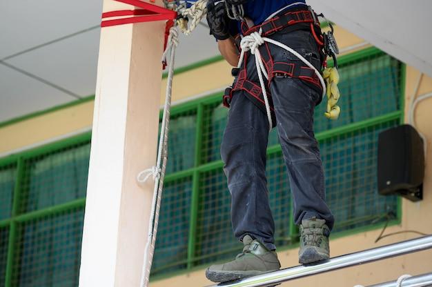 Primo piano di addestramento inferiore del corpo dei vigili del fuoco per esercitazione antincendio dimostrando come fuggire