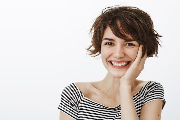 Primo piano di adorabile donna bruna ridendo e arrossendo dal complimento, sorridendo sciocco