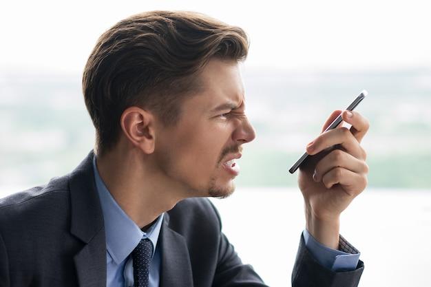 Primo piano di adulti imprenditore arrabbiato con smartphone