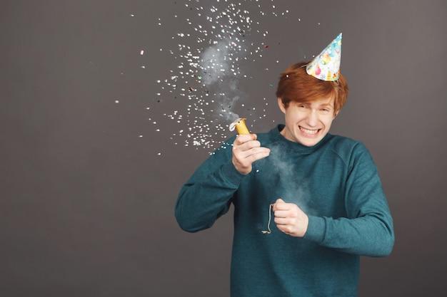 Primo piano di allegro giovane ragazzo dai capelli rossi con taglio di capelli corto in maglione alla moda verde e cappello da festa
