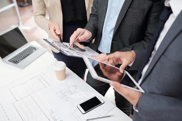 Primo piano di alto angolo del team di affari che lavora al progetto in riunione, mani che tengono tavoletta digitale e grafici di dati, copia dello spazio
