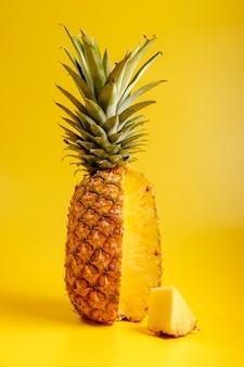 Primo piano di ananas su uno sfondo giallo con pice di ananas