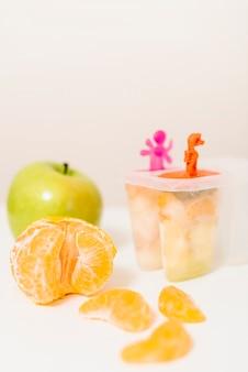 Primo piano di arancia; muffa verde mela e ghiacciolo