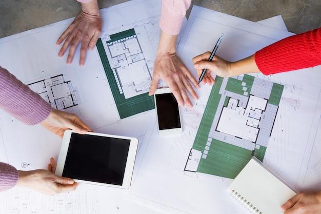 Primo piano di architetti che lavorano con disegni e l'utilizzo di gadget