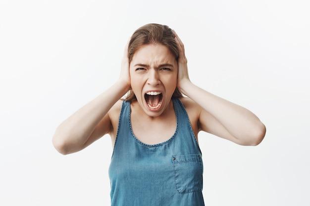 Primo piano di arrabbiata giovane ragazza caucasica con i capelli lunghi scuri che tiene la testa con, urlando con gli occhi chiusi, soffre di mal di testa per la scorsa settimana e non sopporta più ir.