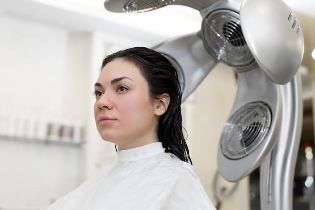 Primo piano di asciugacapelli professionale asciuga i capelli della ragazza