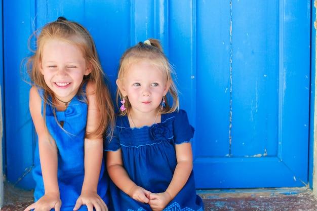 Primo piano di bambine adorabili che si siedono vicino alla vecchia porta blu in villaggio greco, emporio, santorini