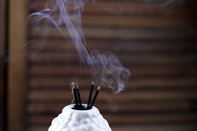 Primo piano di bastoncini di incenso fumo nel vaso