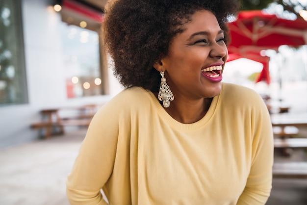 Primo piano di bella donna latina afroamericana che sorride e che passa tempo piacevole alla caffetteria.