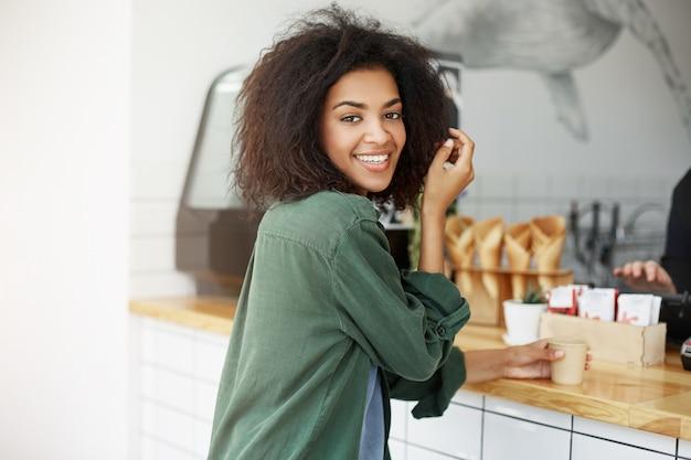 Primo piano di bella donna studentessa africana gioiosa con i capelli ondulati scuri in cardigan verde seduto nella caffetteria, bere una tazza di caffè, sorridente a porte chiuse. donna che aspetta il suo ragazzo dopo l'università.