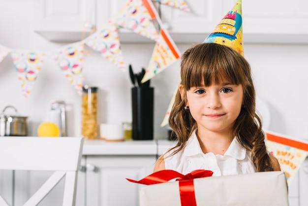 Primo piano di bella ragazza sorridente di compleanno che tiene il contenitore di regalo nella cucina