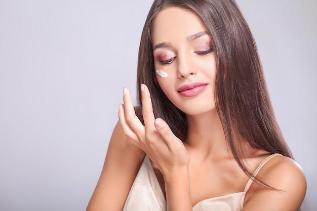 Primo piano di bella ragazza sorridente sexy che mette crema su pelle pura morbida fresca.