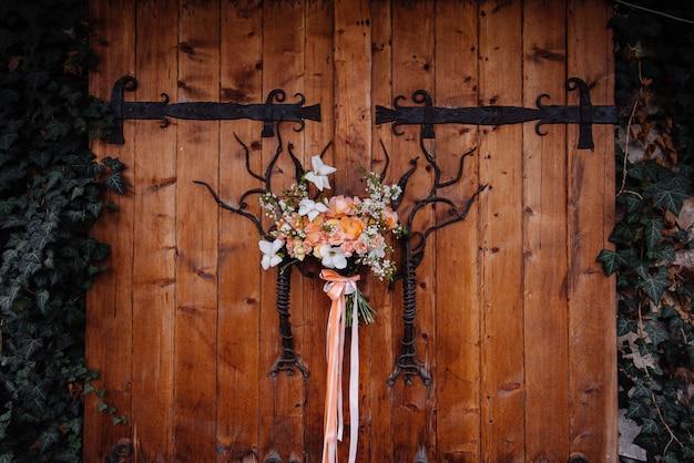 Primo piano di bella sposa elegante bouquet sullo sfondo di un cancello di legno. floristica matrimonio.