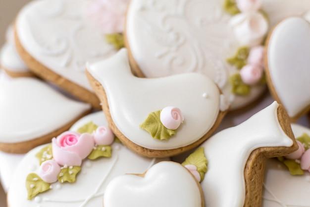 Primo piano di biscotti di panpepato in una glassa bianca, pasticcini alla moda come decorazione per le vacanze,