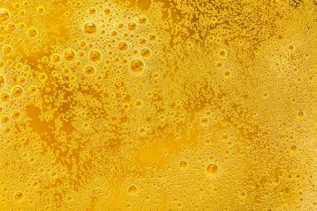 Primo piano di bolle di birra e schiuma come sfondo