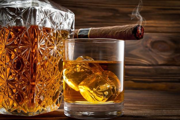 Primo piano di bottiglia, bicchiere con whisky e sigaro fumante
