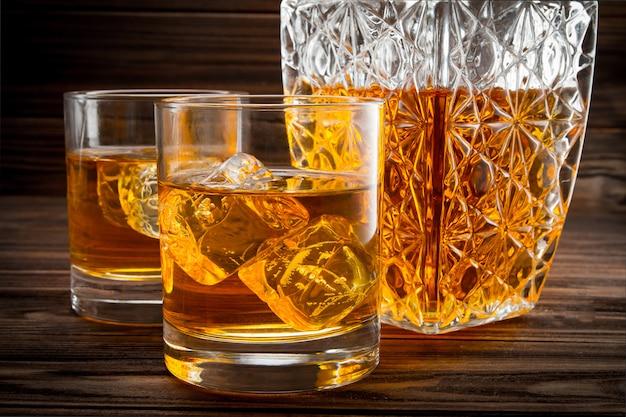 Primo piano di bottiglia e due bicchieri con ghiaccio e whisky