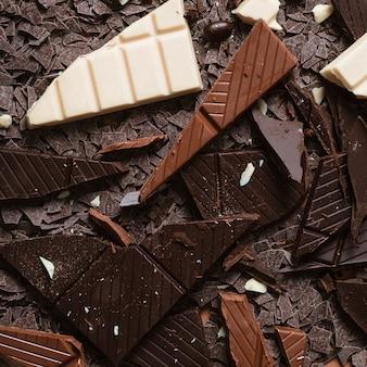 Primo piano di buio; pezzi di cioccolato bianco e marrone