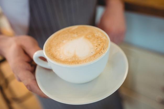Primo piano di caffè servito da cameriera al bar