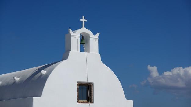 Primo piano di campana, chiesa bianca a oia santorini, grecia.