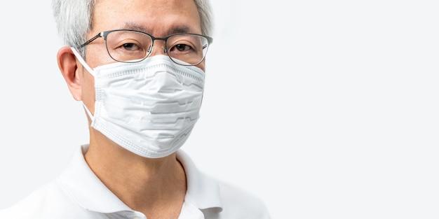 Primo piano di capelli grigi asian man viso con gli occhiali che indossa la maschera bianca n95