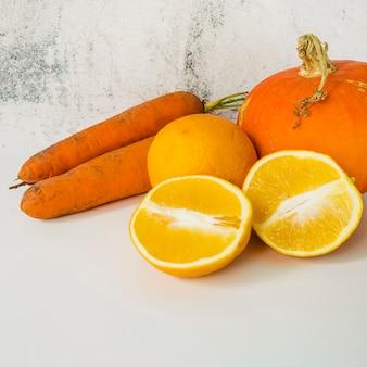 Primo piano di carota; zucca e arance divise a metà su un vecchio fondo strutturato