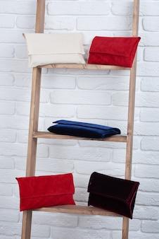 Primo piano di cinque borse da donna alla moda di rosso, bianco, blu e bordeaux, posa sul muro bianco.