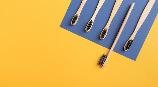 Primo piano di cinque pezzi di spazzolini da denti di bambù su uno sfondo giallo e blu. piatto nero spazzolino da denti in carbonio vulcanico posato con spazio di copia. medicina, concetto ecologico, zero rifiuti.