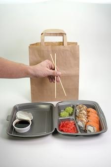 Primo piano di consegna di cibo e rotoli di sushi. il concetto di consegna del cibo