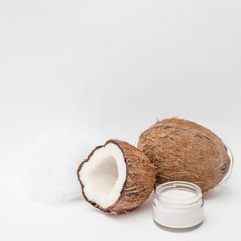 Primo piano di crema idratante; luffa e cocco su sfondo bianco