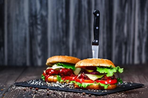 Primo piano di deliziosi hamburger fatti in casa deliziosi con un coltello bloccato sul bordo di pietra. buio