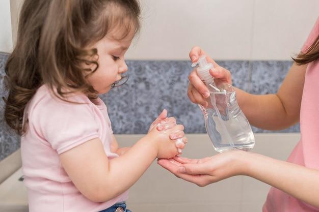 Primo piano di disinfezione delle mani della ragazza