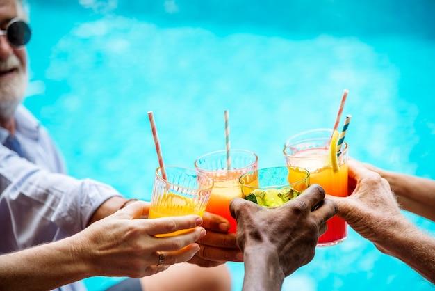 Primo piano di diverse mani tintinnio bevande insieme
