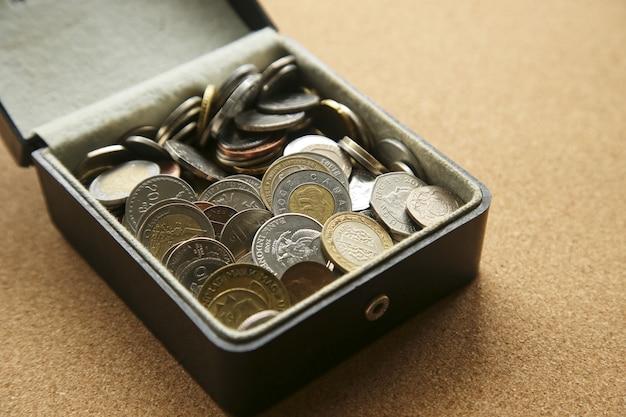 Primo piano di diverse monete in una scatola sul tavolo