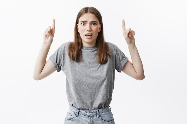 Primo piano di divertente giovane ragazza attraente studente con i capelli scuri in abiti casual con sguardo confuso, rivolto verso l'alto con il dito indice su entrambe le mani. copia spazio.
