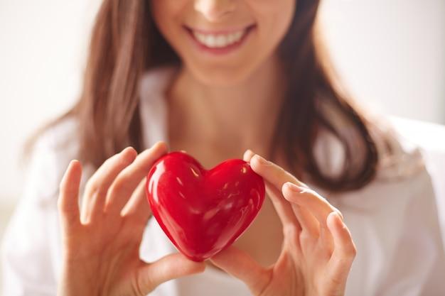 Primo piano di donna che tiene un cuore luminoso