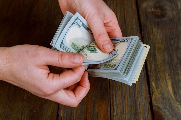 Primo piano di donna d'affari con il conteggio dei soldi mani femminili con denaro contante valuta dollaro usa