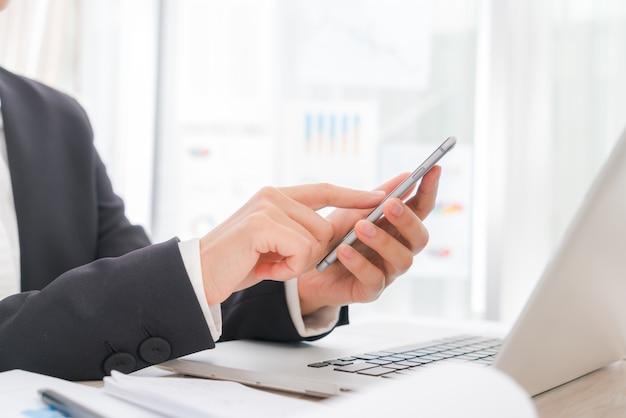 Primo piano di donna d'affari mano digitando sulla tastiera del computer portatile con m