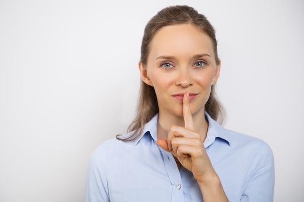 Primo piano di donna sorridente facendo gesto di silenzio