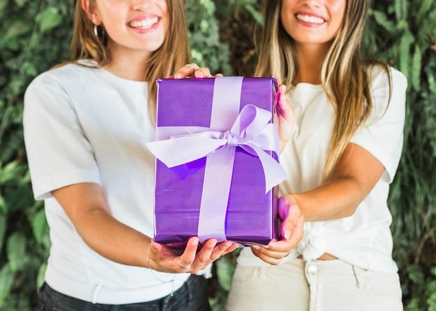 Primo piano di due amici femminili che mostrano il contenitore di regalo viola
