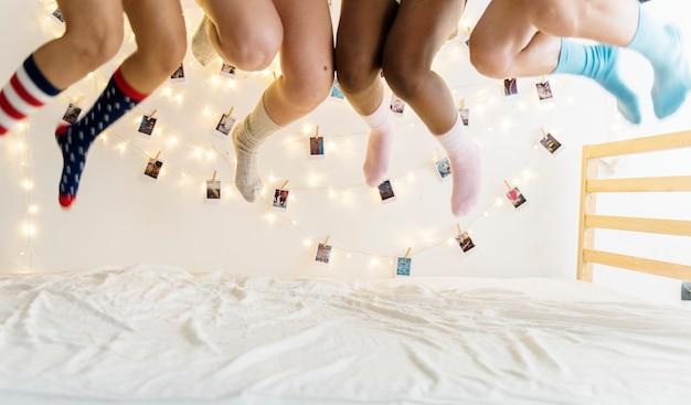 Primo piano di due paia di gambe con calzini saltando sul letto