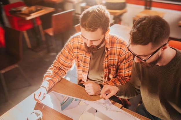Primo piano di due ragazzi adulti e barbuti seduti al tavolo e studiando grafica nei documenti. stanno preparando per demonstation questo materiale.
