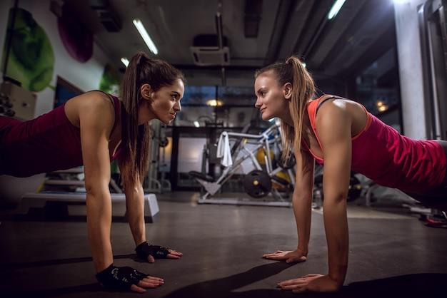 Primo piano di due womans fitness sottile sottile bello facendo push up insieme uno di fronte all'altro e guardarsi in palestra.